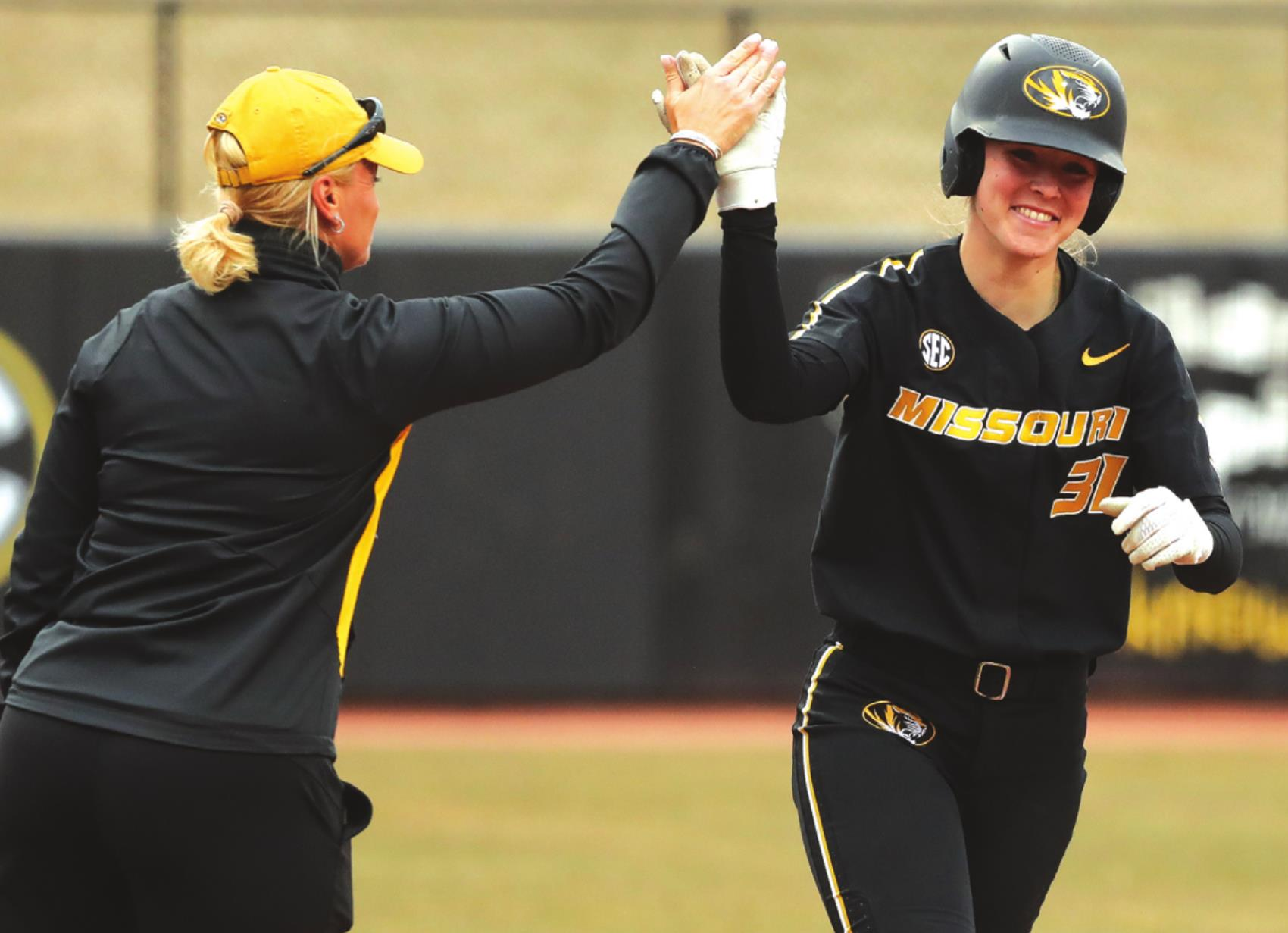 Former La Grange standout Hatti Moore, right, gets a high five from her coach as she trots around third base after a home run. Photos courtesy of University of Missouri