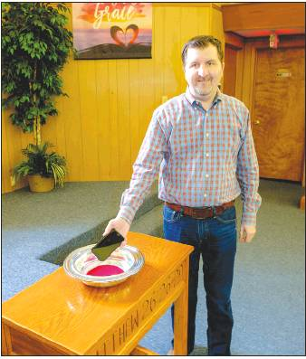 "Rev. Scott Elliott of the La Grange Church of Christ places his cell phone in a collection plate. Elliott and his fellow religious leaders in the La Grange Area Ministerial Alliance are encouraging everyone to participate in a ""technology fast"" during Holy Week, April 13-20.            Photo by Andy Behlen"