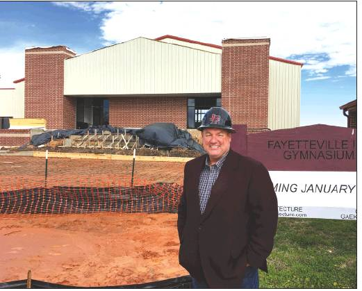 Fayetteville superintendent Jeff Harvey stands in front of the school's new $4.9 million gym, expected to be completed by March.            Photo by H.H. Howze