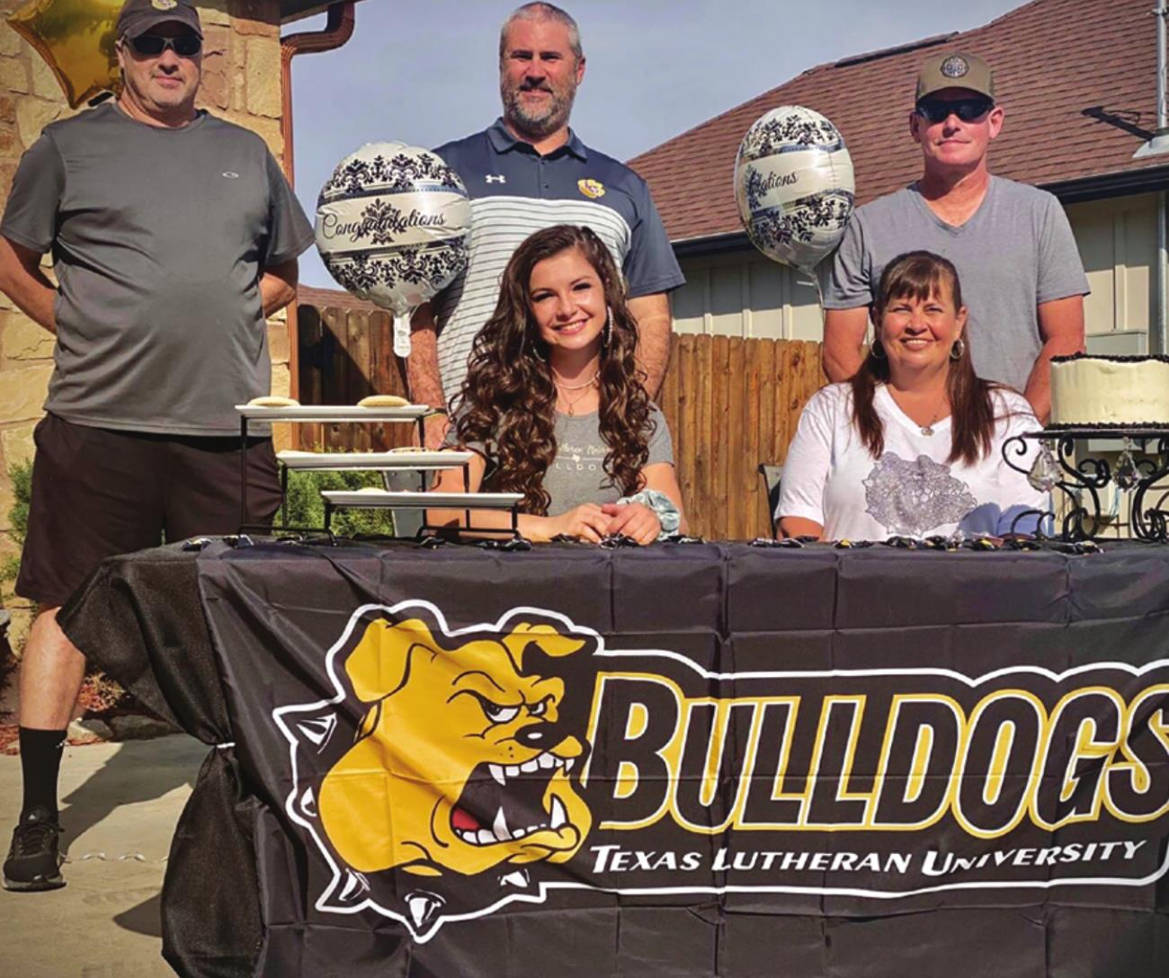 Brenna Iannelli is shown, above left, standing alongside the various jerseys she wore and the medals she won as a La Grange athlete. Right, is a photo of her at her signing ceremony this weekend. Pictured (back, from left) are Coach Chris Westall, Coach Eric Amick, Father Doug Iannelli. Front row; Brenna Iannelli, and Mother Shay Iannelli.